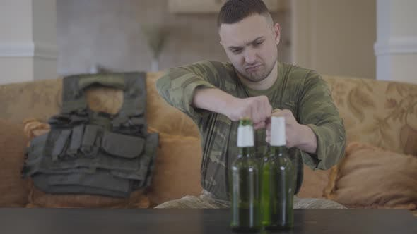Thumbnail for The Man in Military Closes Opening Beer Sitting at Home on the Sofa. Unhappy Man