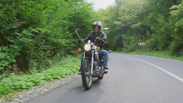 Thumbnail for Young man riding a motorcycle on a forest road