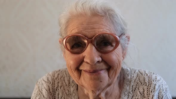 Thumbnail for Slow Motion Portrait of a Happy Senior Woman with Gray Hair and Glasses.