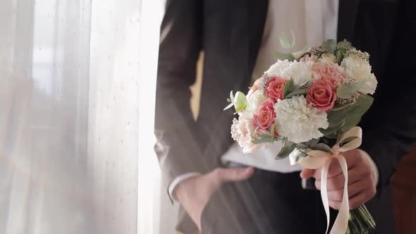 Thumbnail for Groom with Wedding Bouquet in His Hands at Home. White Shirt, Jacket