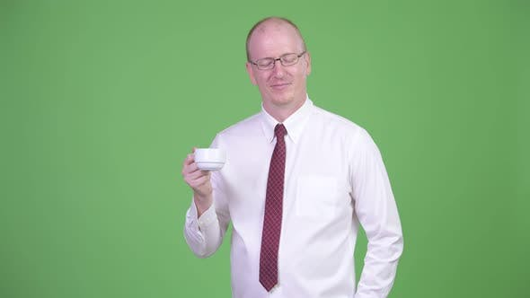 Thumbnail for Mature Bald Businessman Turning Coffee Cup Upside Down