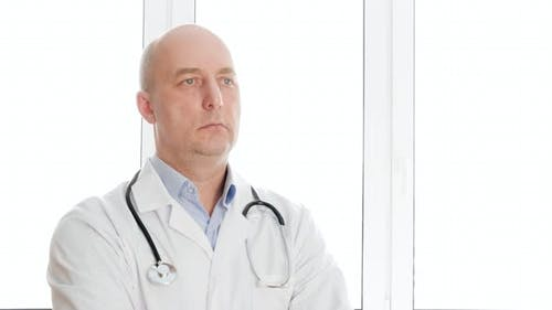 Portrait Doctor in White Lab Coat with Phonendoscope Nodding Head in Clinic Office. Practitioner