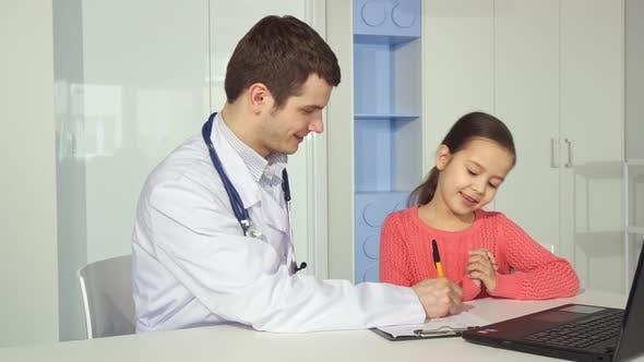 Kinderarzt zeichnet auf Zwischenablage in der Nähe der kleinen Mädchen