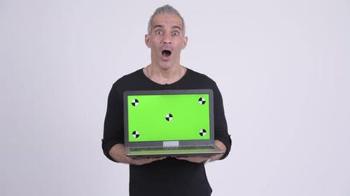 Handsome Persian Man Showing Laptop and Looking Surprised