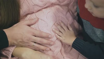 Big and Small Hands on Pregnant Woman Belly in Pullover
