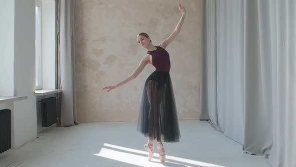 Performance of a Fragile Ballerina Against the Background of Large Panoramic Windows and Curtains