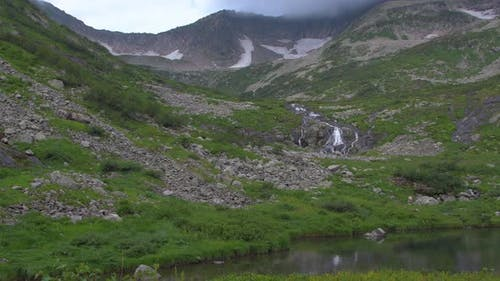 Lake in Mountain Valley. Stream on Side of Hill