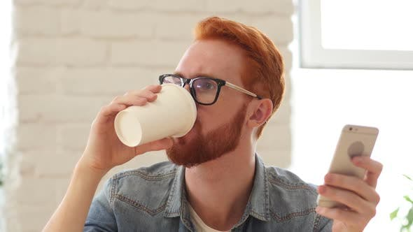 Cover Image for Man with Beard and Red Hairs Using Smartphone, Phone and Drinking Coffee, Tea