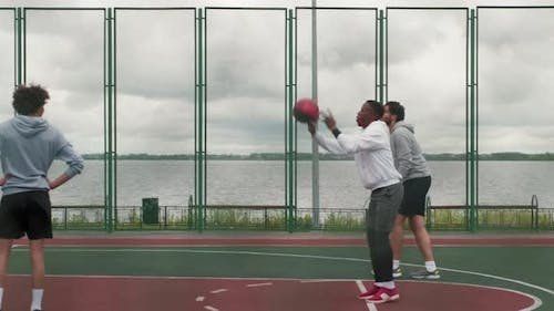 Friends Shooting Hoops on Outdoor Basketball Court