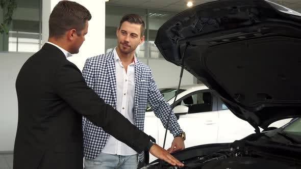 Thumbnail for A Professional Salesman Acquaints a Buyer with a Car Engine