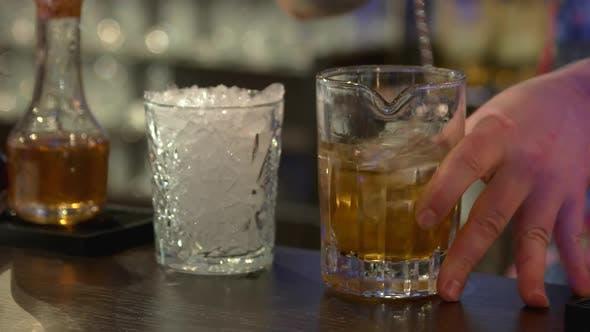 Rum mit Eis im Glas mischen.