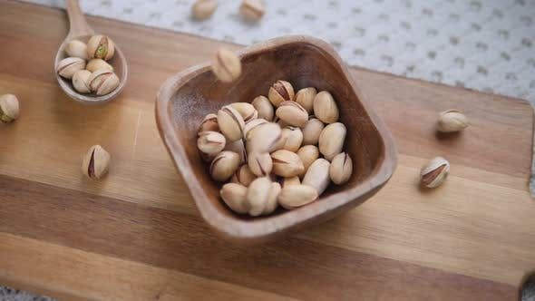 Thumbnail for Wooden Bowl With Pistachios On Wooden Board.