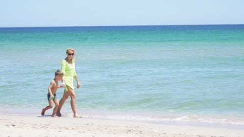 Little Boy Holding His Mother's Hand Walks Along the Sandy Shore of the Azure Sea