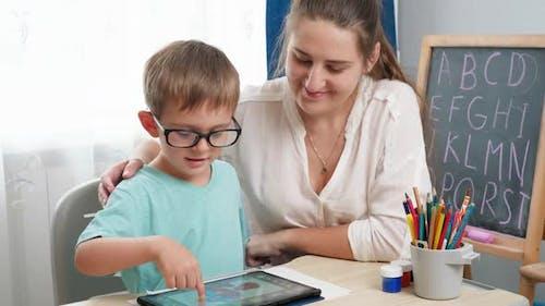 Kleiner Junge in Brillen spielt auf Tablet Computer