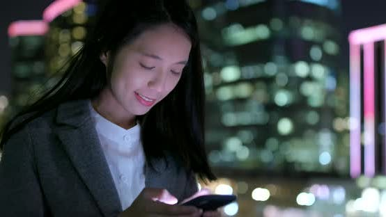 Thumbnail for Businesswoman use of cellphone in city at night