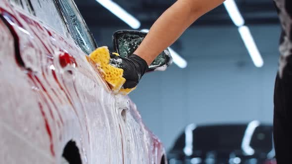 Auto Cleaning Service  Man Cleaning the Car Surface with a Yellow Sponge