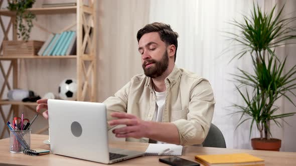 Exhausted Freelancer Tired of Work and Closes Laptop in Home Office
