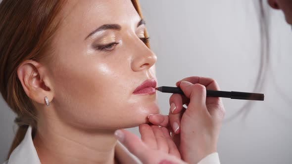 Master Is Outlining Model Lips By Cosmetic Pencil, Close-up