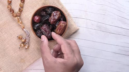 the Concept of Ramadan, Hand Pick Date Fruit From a Bowl