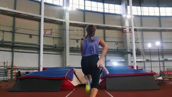 Thumbnail for Pole Vaulting in the Indoors Stadium - Young Woman with Pigtails Jumping Over the Bar and Falling