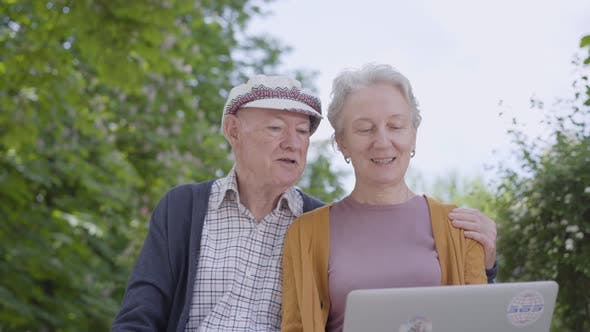Thumbnail for Old Woman with Grey Hair and Old Man in Cap Sitting in the Bench in the Beautiful Park and Talking