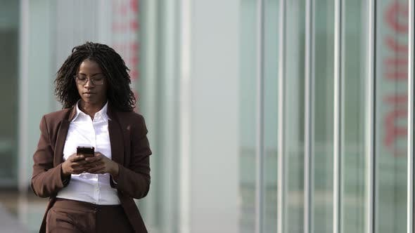 Concentrated Businesswoman with Dreadlocks Talking on Smartphone
