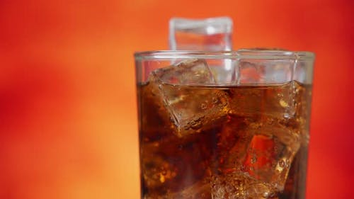 Cola avec des glaçons tourner en gros plan. Cola avec de la glace et des bulles en verre. Gros plan de soda.