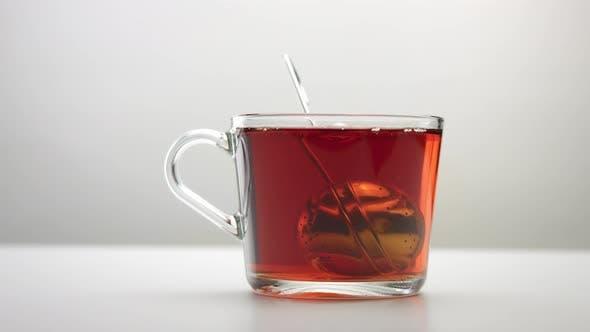 Thumbnail for Ein Tee-Ei Löffel bewegt sich in Zeitlupe in eine transparente Teetasse