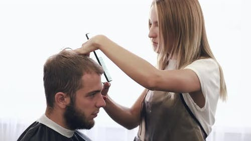 Female Stylist Doing Haircut for Client in Beauty Salon