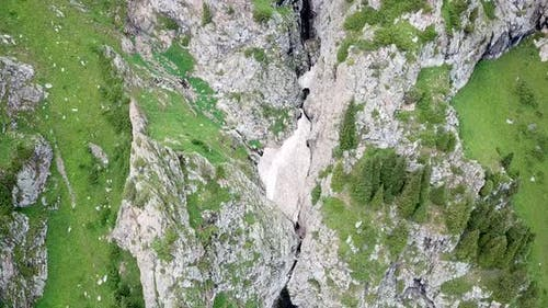 Top View of Steep Mountain Cliffs and an Ice Cave