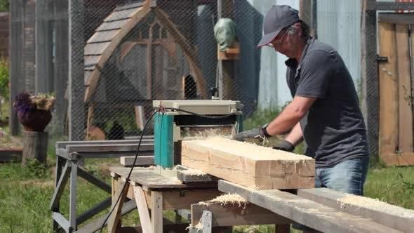 Thumbnail for Carpenter planing wooden beam