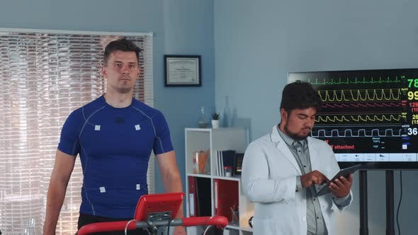 Thumbnail for Mixed Race Doctor Performing Stress Test While the Athlete Walking on Treadmill