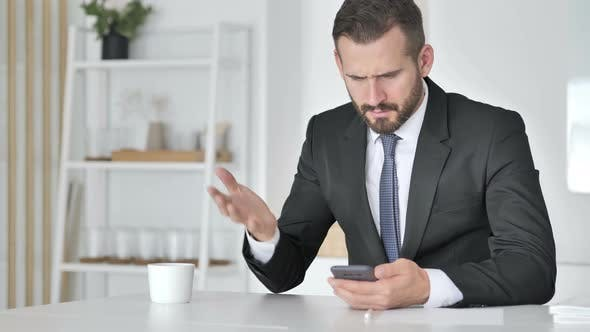 Astonished Businessman Shocked By Result on Smartphone, Wondering