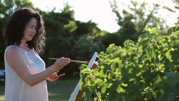 Female Artist Painting a Colorful Painting Outdoors