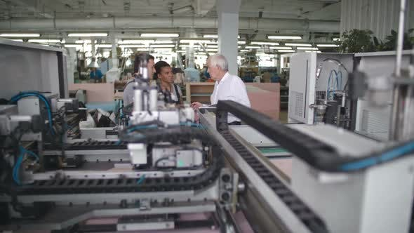 Workers Discussing Automated Machinery