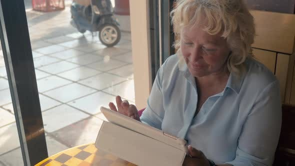 Cover Image for Mature Woman Sitting in a Cafe and Enjoys Her Tablet., Outside the Window the Summer, Sunny Day