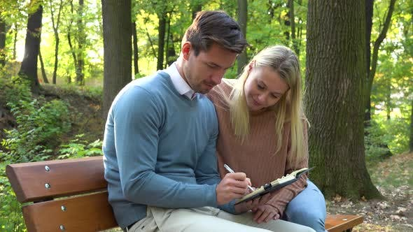 Thumbnail for A Young Attractive Couple Sits on a Bench in a Park on a Sunny Day, the Man Writes Into a Notepad