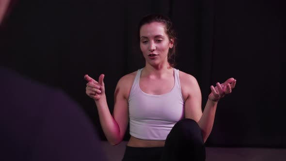 Pretty Yoga Coach Tells the Basic Rules of the Class