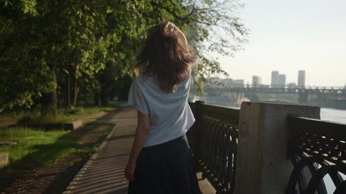 a Brunette in Casual Clothes Goes and Touches Hair in a City Park Near an Openwork Lattice