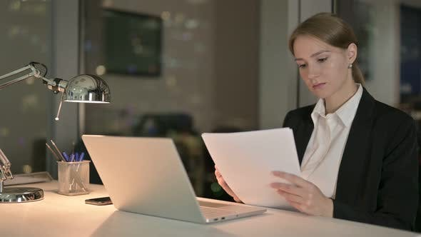 Thumbnail for Ambitious Businesswoman Reading Document on Office Desk at Night