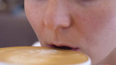 Close Up of Female Mouth Drinking Coffee Latte Carefully