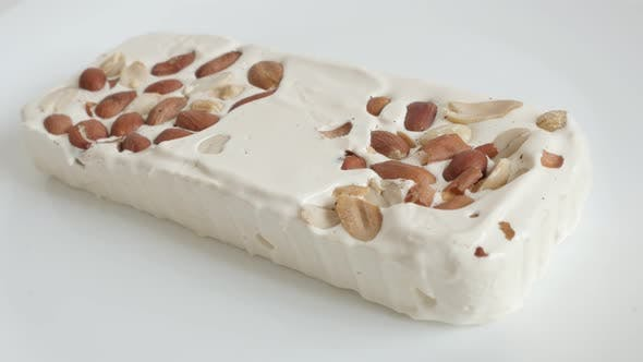 Thumbnail for Nougat halva with almonds on white 4K video