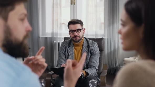 Bärtige Psychologe beobachtet, wie seine Patienten ihre Beziehungen während des Besuchs im Büro herausfinden