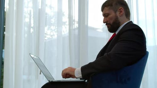 Serious Bearded Businessman Working on Laptop Computer in Office Lobby