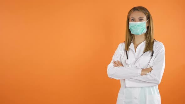 Women Doctor with Face Mask Smiles in Front of the camera.Orange Studio Background Copy Space
