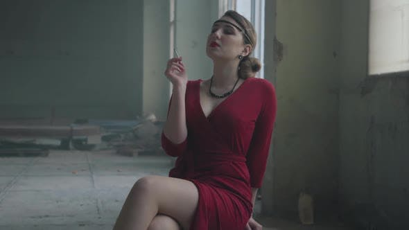 Thumbnail for Elegant Woman in Red Elegant Dress Sitting on the Chair in the Abandoned Building Smoking Cigarette