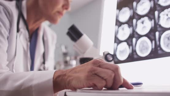 Thumbnail for Intelligent female radiologist analyzing with microscope