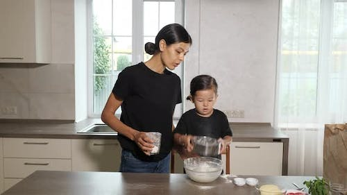 Mother and Daughter Wearing Black Shirts and Same Hairstyle