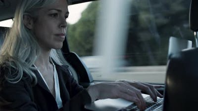 Grayhaired Woman in Official Suit Typing on Laptop in Car