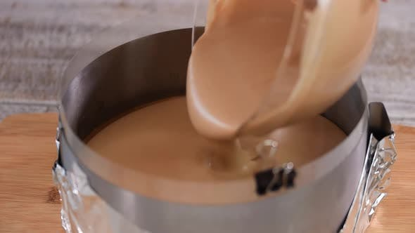 Confectioner Pouring Chocolate Mousse Into A Pastry Ring.